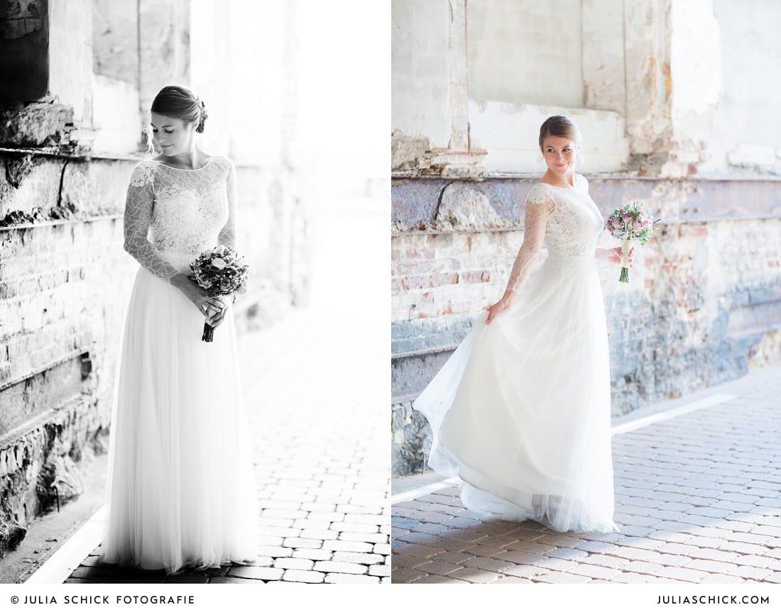 Braut in Hochzeitskleid von Anna Kara vor Ziegelwand mit Stahlträgern am Factory Hotel in Münster