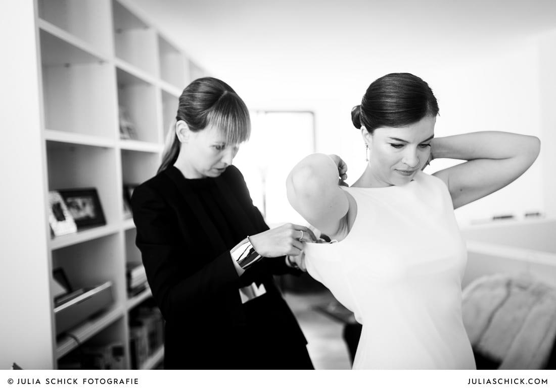 Trauzeugin hilft Braut beim Ankleiden vor kirchlicher Trauung