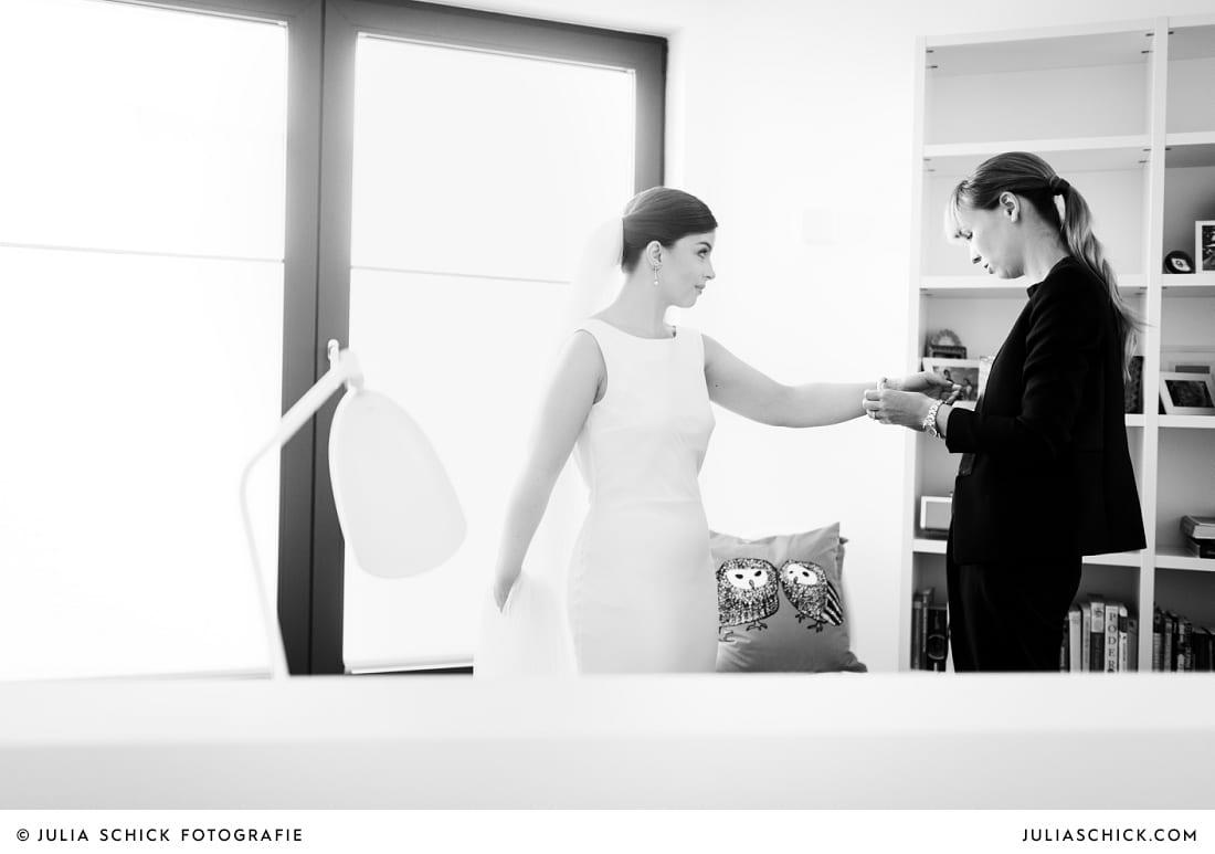 Trauzeugin hilft Braut beim Ankleiden
