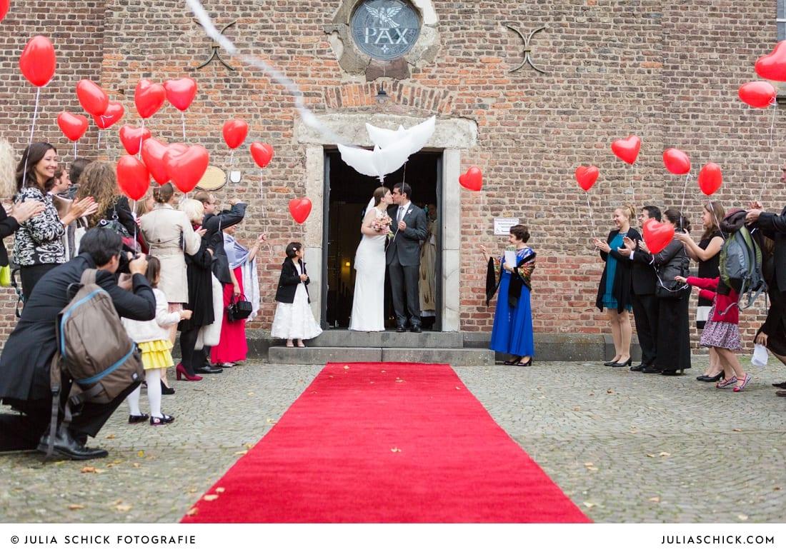 Brautpaar mit Luftballons steht im Portal der Sankt Antonius Kirche in Leverkusen Wiesdorf