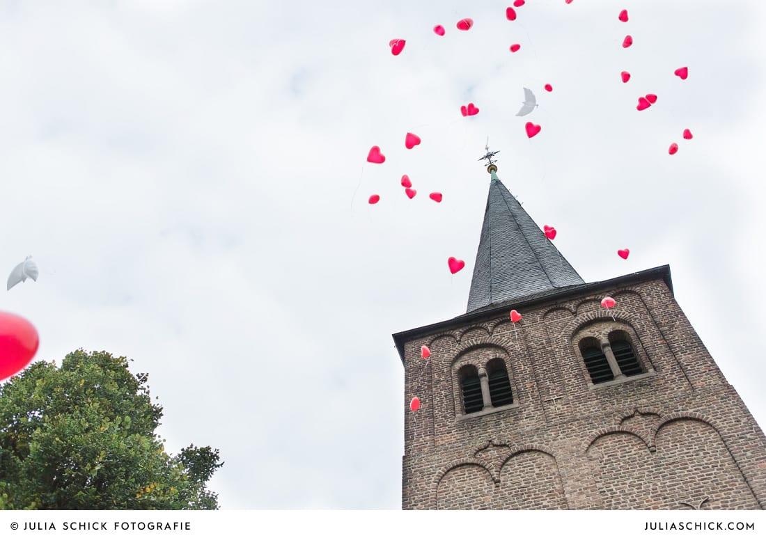 Luftballons vor Kirchturm der Sankt Antonius Kirche in Leverkusen Wiesdorf