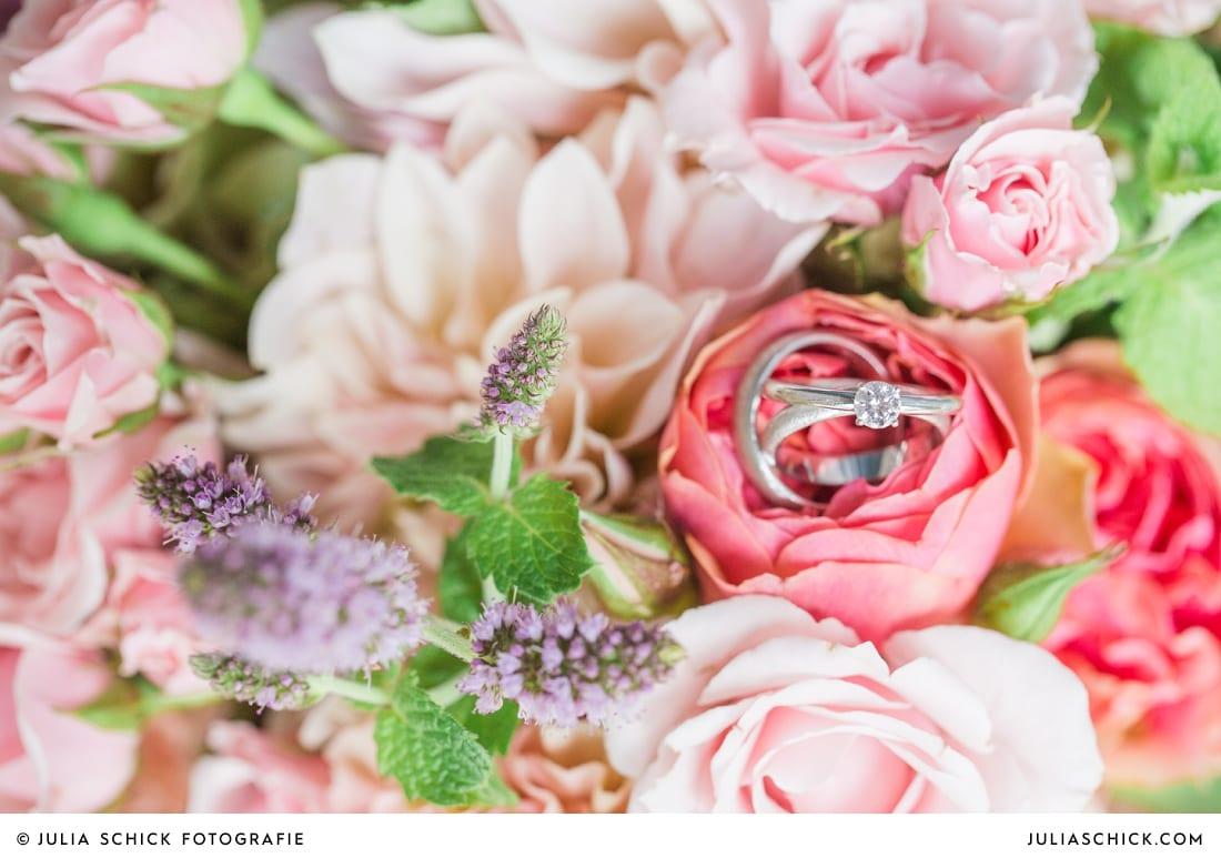 Detailaufnahme von Eheringen und Verlobungsring auf rosa-pfirsichfarbenen Brautstrauß mit Rosen, Nelken und Minze
