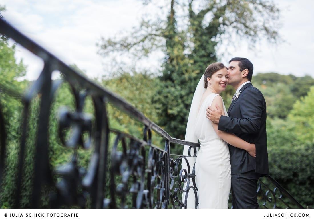 Bräutigam küsst Braut auf Schläfe auf Schloss Eicherhof in Leichlingen