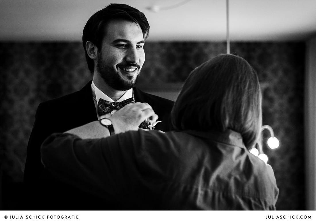 Brautmutter steckt Bräutigam vor Hochzeit in Lüdinghausen Blumenanstecker an