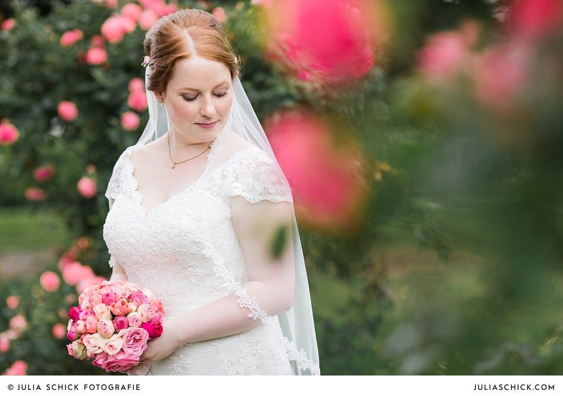 Braut umgeben von Rosen bei Hochzeitsfotoshooting im Rosengarten Seppenrade