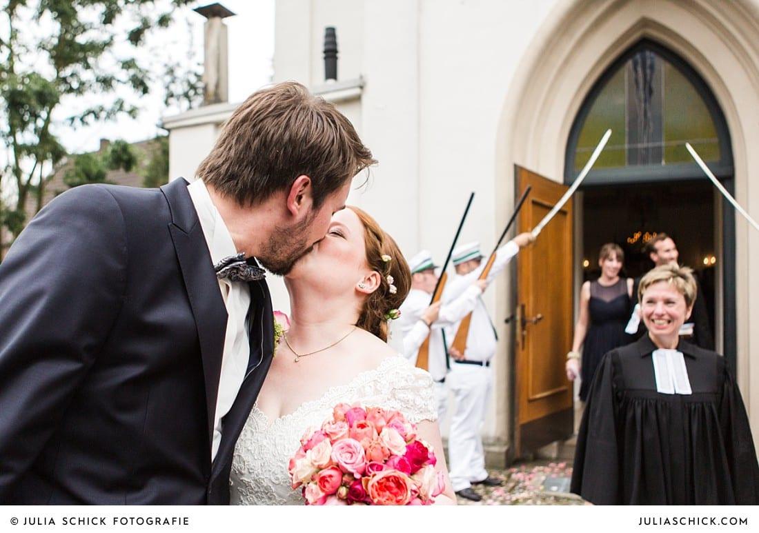 Küssendes Brautpaar vor der evangelischen Kirche in Lüdinghausen