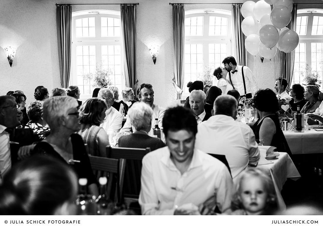 Küssendes Brautpaar während Abendessen bei Hochzeitsfeier auf Frenkings Tenne in Aschberg