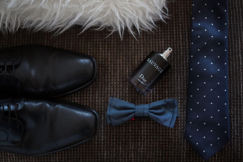 Detailfoto der Accessoires des Bräutigams bestehend aus schwarzen Schuhen, Fliege, Herrenparfüm und Krawatte