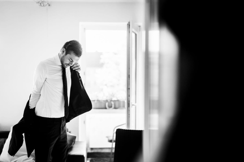 Bräutigam zieht sich die Anzugsjacke seines dunkelblauen Hochzeitsanzugs an