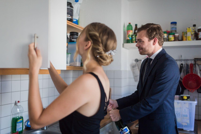 Brautjungfer sucht im Schrank nach Sektgläsern während Bräutigam die SEktflasche öffnet