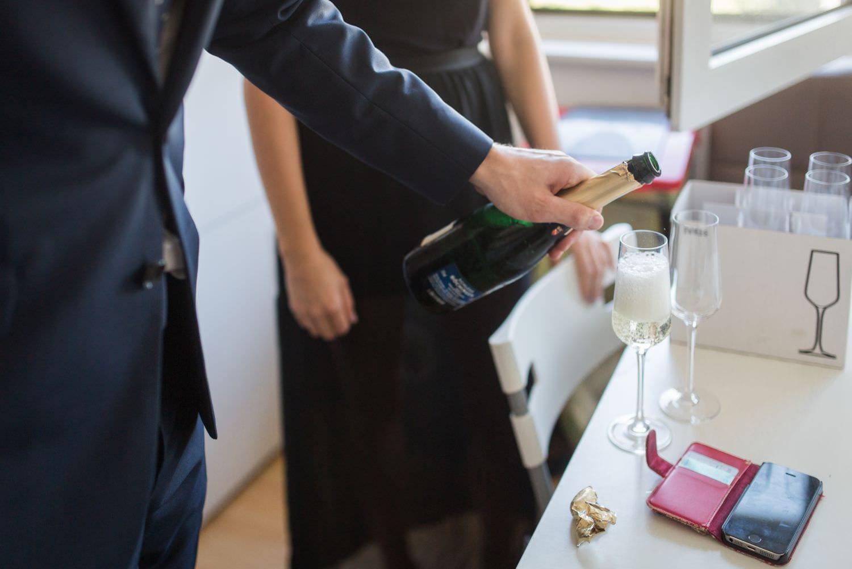 Bräutigam schenkt beim getttiing ready Sekt ein
