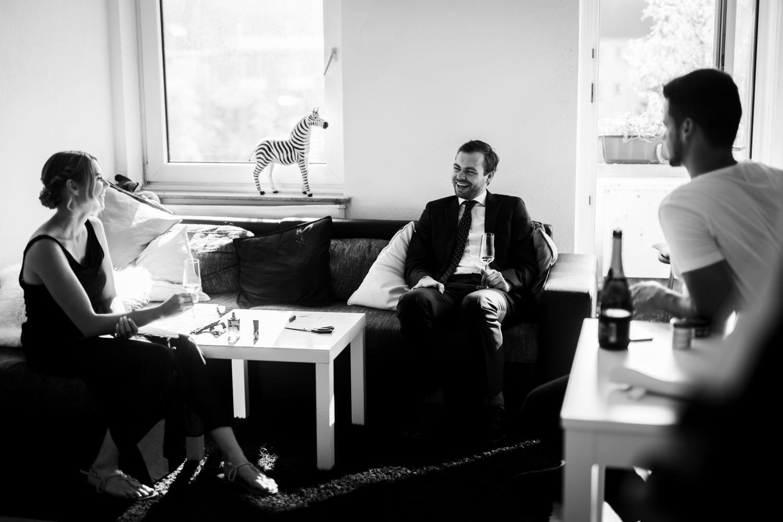 Bräutigam sitzt auf Sofa und trinkt Sekt vor der kirchlichen Trauung in Münster