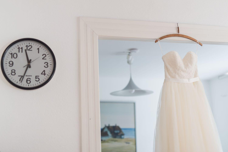 Brautkleid hängt in einer Tür, daneben ist eine Uhr zu sehen