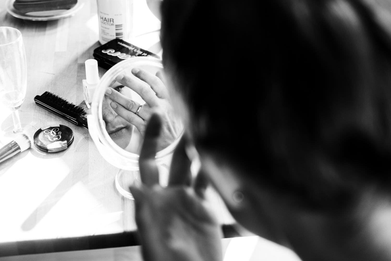 Braut schaut bei Hochzeit in Münster in den Spiegel und bereitet ihr Brautstyling vor