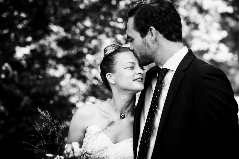 Bräutigam gibt Braut beim Hochzeitsfotoshooting in Münster LKuss auf die Stirn