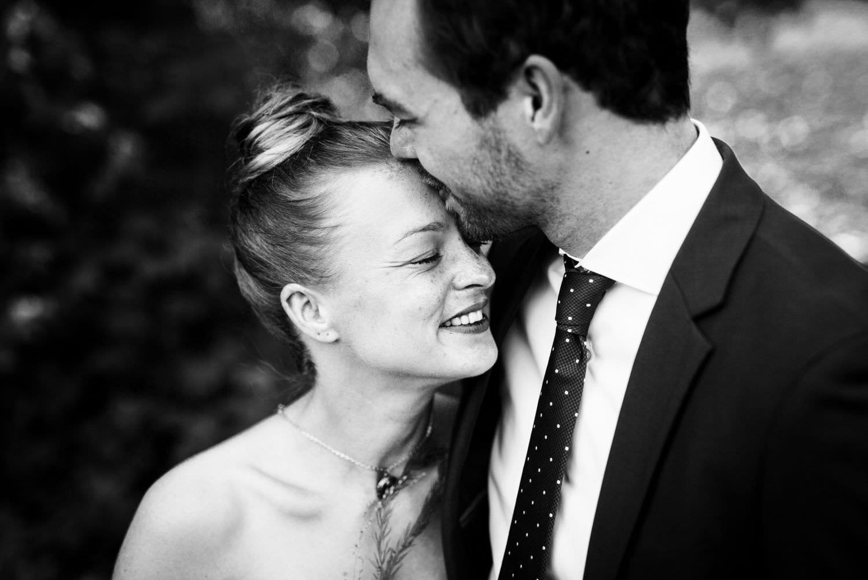 Bräutigam küsst Braut bei Hochzeitsfotoshooting an der Dyckburgkirche in Münster auf die Stirn