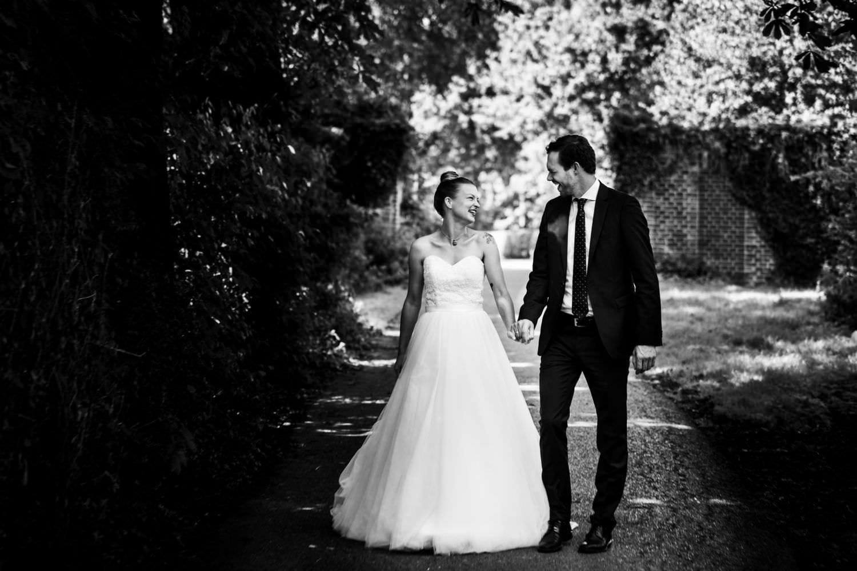 Braut und Bräutigam gehen durch den Wald an der Boniburg in Münster