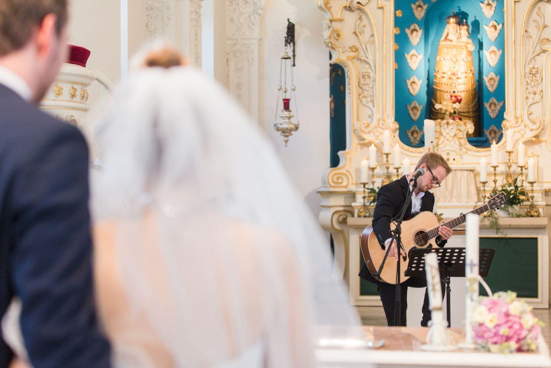 Bruder der Braut spielt Gitarre bei kirchlicher Trauung in der Dyckburgkirche in Münster