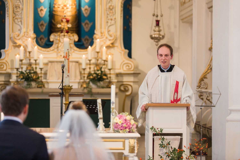 Pfarrer im Ornat bei kirchlicher Trauung liest Bibelvers in der Dyckburgkirche in Münster
