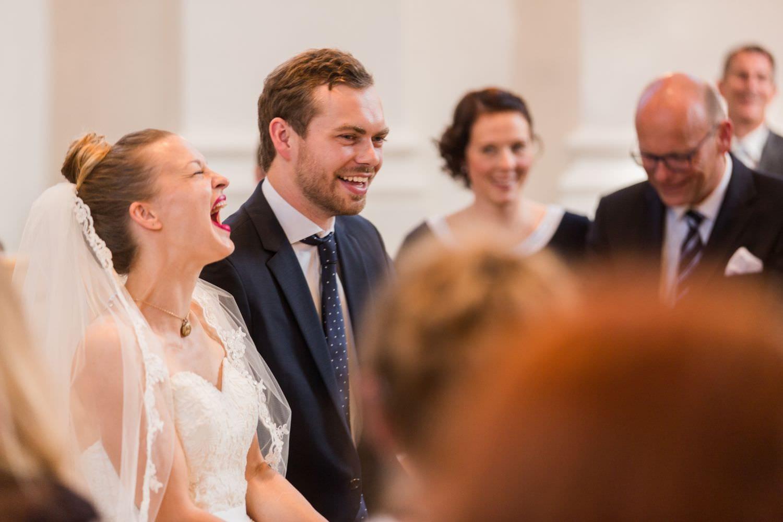Lauthals lachendes Brautpaar bei kirchlicher Trauung in der Dyckburgkirche in Münster Handorf