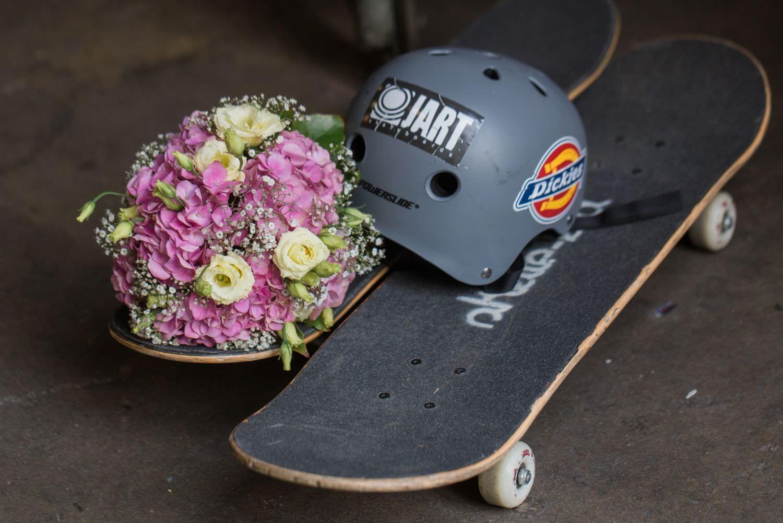 Brautstrauß und Helm liegen auf Skateboard bei Hochzeitsfeier im Skaters Palace in Münster