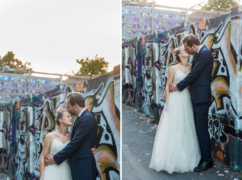 Brautpaar bei Hochzeitsfotoaufnahmen an Mauer mit Grafiti am Skaters Palace im Südviertel gelehnt