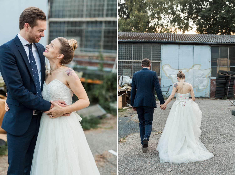 Tätowierte Braut und Bräutigam im blauen Anzug auf dem Weg zum Hochzeitsfotoshooting vor blauem Tor am Skaters Palace in Münster