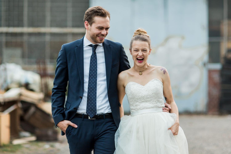 Lachendes Brautpaar vor blauem Tor in der Nähe des Skaters Palace in Münster