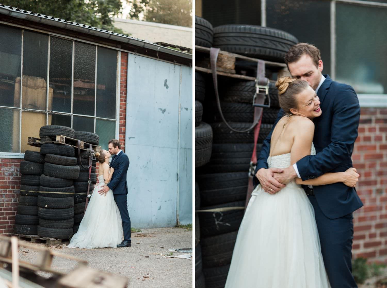 Schmusendes Brautpaar vor Reifenstapel bei alternativem Hochzeitsfotoshooting am Skaters Palace in Münster