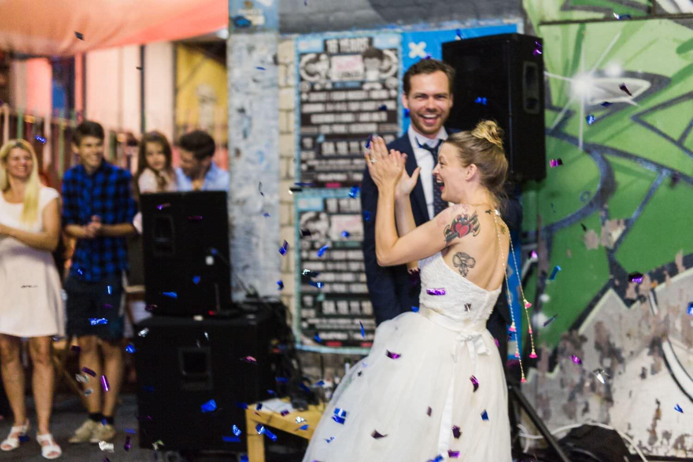 Tätowierte Braut klatscht begeistert umgeben von Konfetti