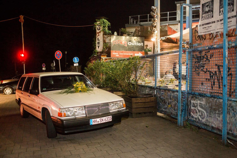 Alter Saab als Brautauto mit gelbem Blumenschmuck steht vor dem Tor des Skaters Palace in Münster