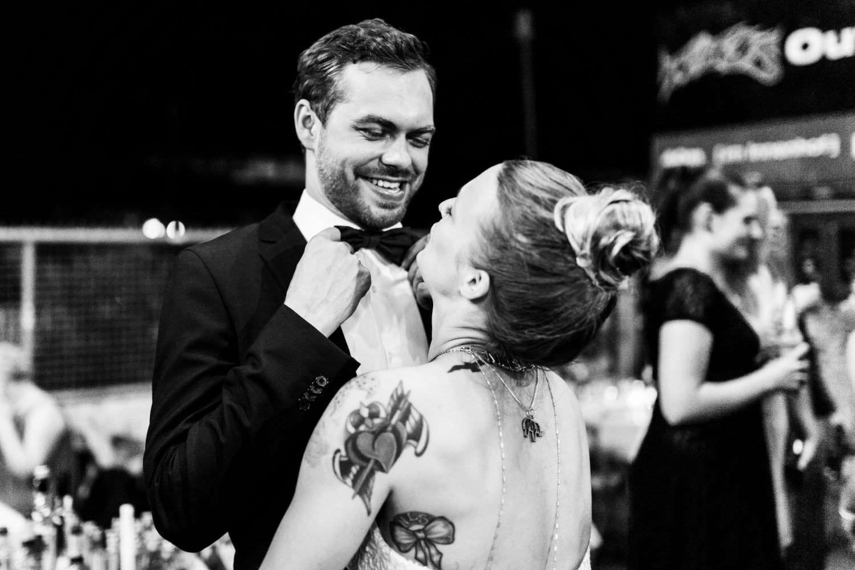 Bräutigam zeigt seiner tätowierten Braut stolz seine Fliege bei Hochzeitsfeier im Skaters Palace in Münster