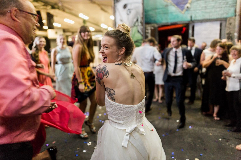 Tättowierte Braut tanzt wild mit Hochzeitsgast auf der Fläche vor dem Skaters Palace in Münster
