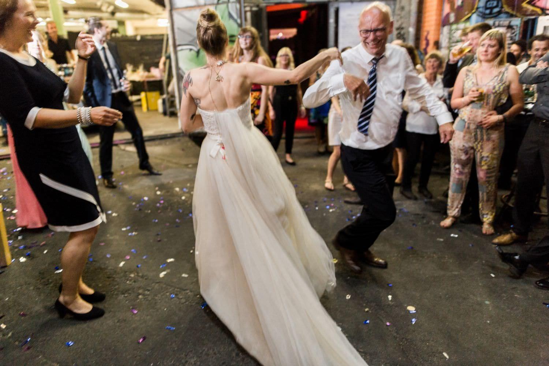 Braut und Hochzeitsgast tanzen wild auf der Tanzfläche vor dem Skaters Palace in Münster