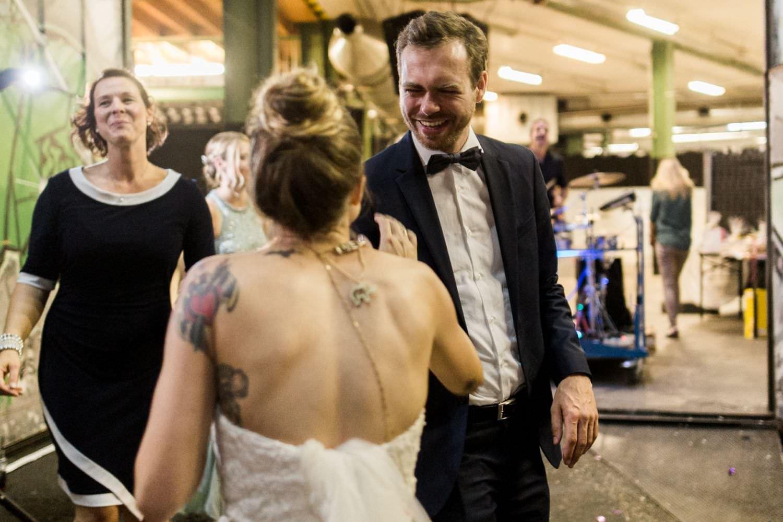 Bräutigam lacht Braut an während beide auf Hochzeitsfeier vor dem Skaters Palace in Münster tanzen