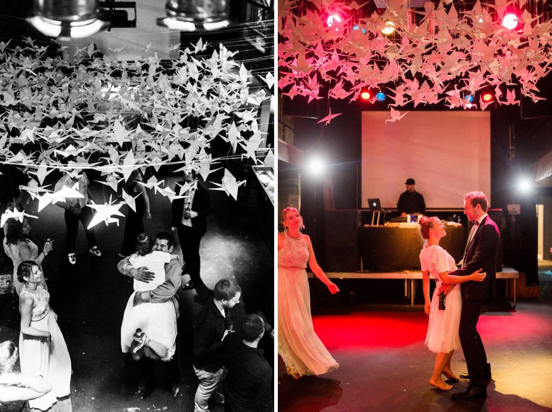 Braut umarmt Gast und tanzt mit Bräutigam unter 1000 Kranichen auf Tanzfläche im Skaters Palace