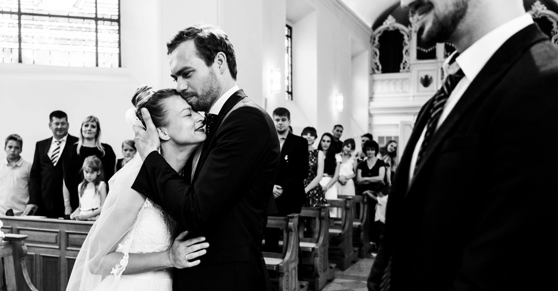Bräutigam nimmt Braut bei kirchlicher Trauung in der Dyckburgkirche in den Arm