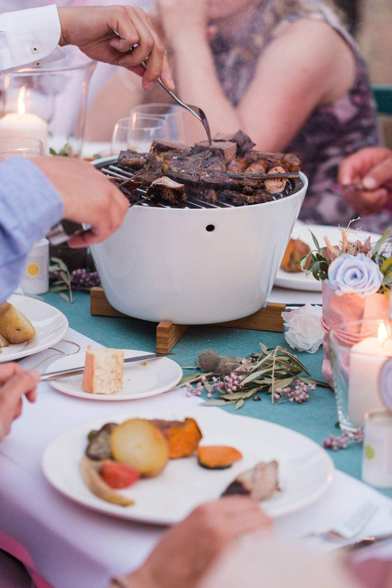 Tischgrill mit Fleisch auf einem festliche dekorierten Tisch in Pastelltönen bei einer Hochzeit im Casal Santa Eulalia auf Mallorca